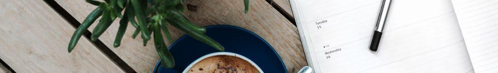 Kalender und Kaffee auf dunklem Tisch mit Blume